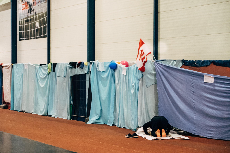 Ein Moslem nimmt sich die Zeit und geht seinem Gebet nach. Es ist kurz vor fünf Uhr Nachmittags. Stiegl-Fahnen haben die Flüchtlinge von einem der Fussballspiele mitgebracht, für die sie regelmäßig Freikarten geschenkt bekommen.