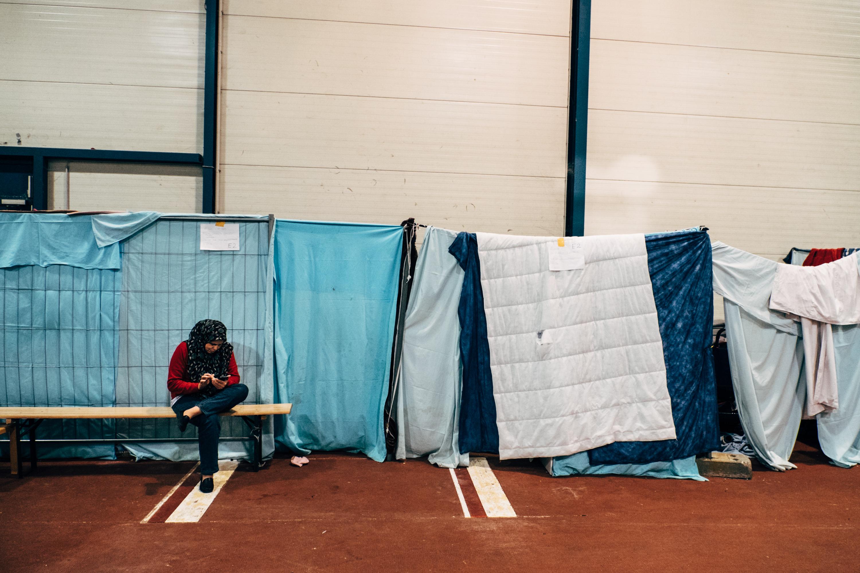 Eine Frau sitzt alleine vor ihrer Behausung in der Familien-Halle neben dem Ferry-Dusika-Stadion und tippt auf ihrem Handy herum.